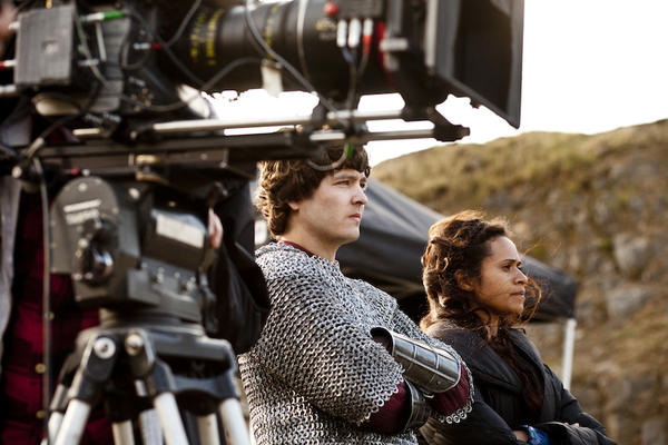 "Alexander Vlahos, who plays Mordred in ""Merlin,"" and Angel Coulby (Gwen) watch their co-stars during filming."