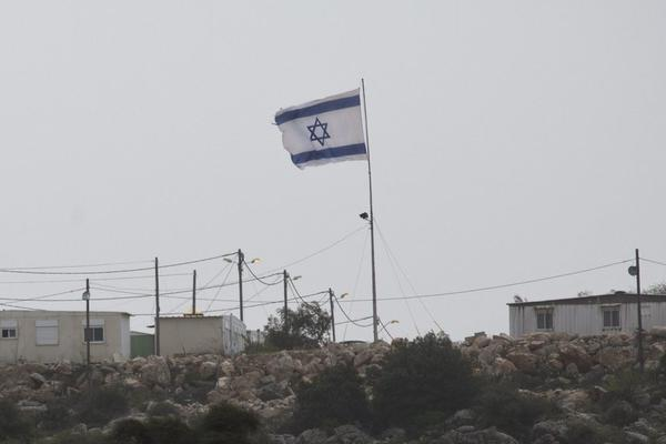 A large Israeli flag flies near a small Jewish settlement of Ha Tamar, just outside the large Efrat settlement in the West Bank.