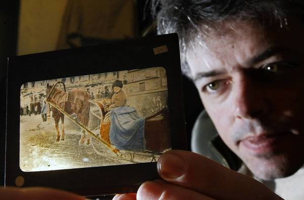 "Anton Orlov holds a 1917 ""magic lantern"" slide from Russia, part of a treasure trove of images he obtained from the grandaughter of a man who took them during the revolution."