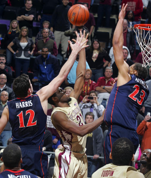 Florida State Seminoles guard Michael Snaer (21) gets between Virginia Cavaliers guard Joe Harris (12) and guard Justin Anderson (23) to hit the game-winning shot with 4.4 seconds left in the second half of their game at the Donald L. Tucker Center. The Florida State Seminoles beat the Virginia Cavaliers 53-51.