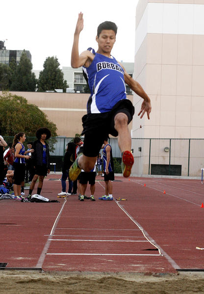 "Burbank's Dennis Talacio, 17, jumps 19' 8"" in the long jump against Hoover in a Pacific League dual track and field meet at Burbank High School on Thursday, March 7, 2013. Talacio won the high hurdles and 300 meter low hurdles, and also competed in the triple jump."