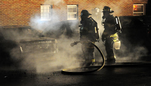 Allentown Firefighters work on extinguishing hot spots in three cars that caught on fire in the St. Lukes Hospital Parking lot B along North St. Cloud Street between 17th and 18th Streets in Allentown Thursday night.