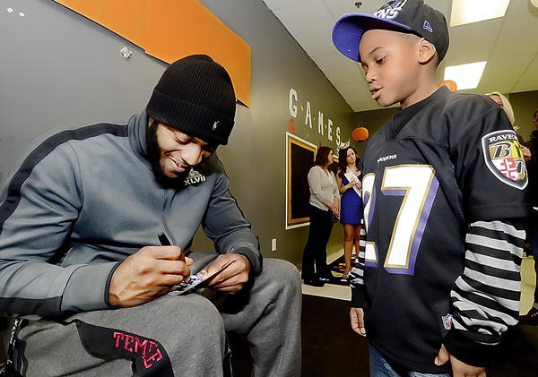 Baltimore Ravens running back Bernard Pierce signs a autograph for Linwood Racks III at The Baby Sitter Child Care Enrichment Center on Northern Avenue on Thursday.  Middle- and high-school-aged youngsters from the Leading4Life Mentoring Program were on hand to hear the member of the Super Bowl championship team speak.