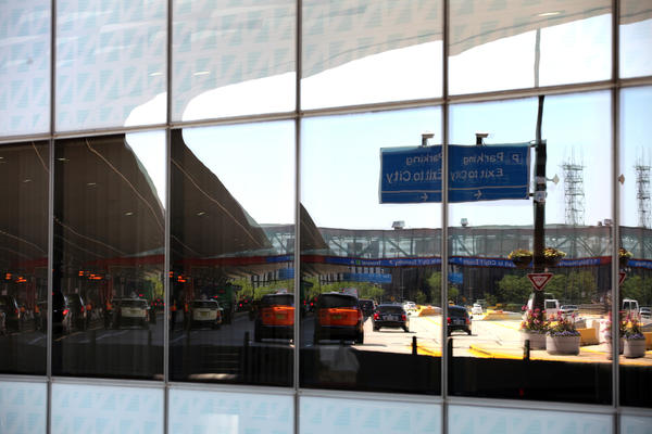 Cars on the departure level at O'Hare International Airport are reflected int he glass buildings of the airport in 2012.