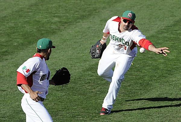Adrian Gonzalez of Mexico and the Dodgers flips the ball to pitcher Sergio Romo for a forceout at first in Mexico's 6-5 loss to Italy in its World Baseball Classic opener on Thursday.