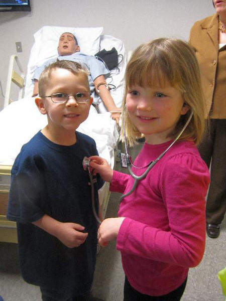 Sheridan Elementary student Bobby Patrick (left) plays patient for fellow student Arden Copeland as she practices taking a heartbeat with a stethoscope during a recent trip to the new North Central Michigan College Health Education and Science Building. Stan the mannequin is in the background.