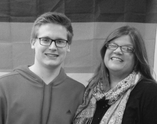 German foreign exchange student Vincent Wasserfuhr (left) poses with his first Petoskey mom, Sherry McGuffin, in front of the German flag he gave to his history teacher Jodie Anderson. Vincent is completing his junior year at Petoskey High School sponsored by Rotary Club of Petoskey.