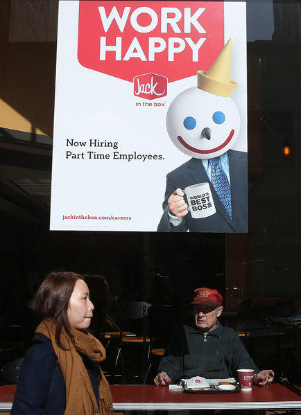 A sign advertising jobs in the window of a Jack in the Box restaurant in San Francisco.