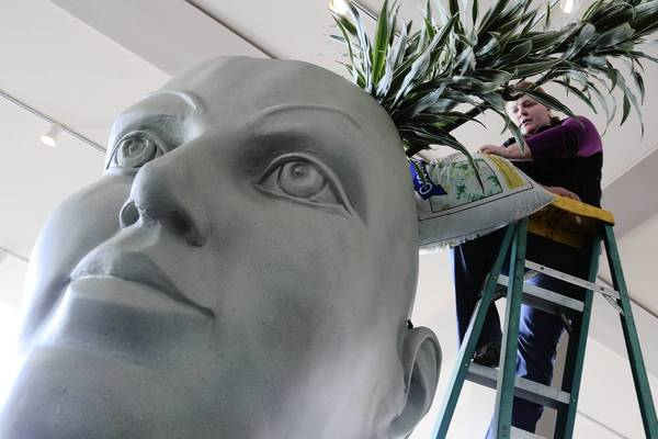 Carrie Hancock pours in bags of soil mix as she prepares a 7-foot  planter head that will greet attendees at the annual Chicago Garden and Flower Show at Navy Pier.