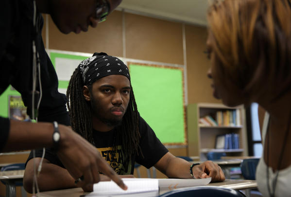 Kenwood Academy student Omari Ferrell goes over his poem with former students and coaches Slayton Goodman, center, and Ashaki Howard, while preparing for the annual Louder Than a Bomb poetry tournament, Thursday Feb. 21,  2013. (Abel Uribe/ Chicago Tribune)