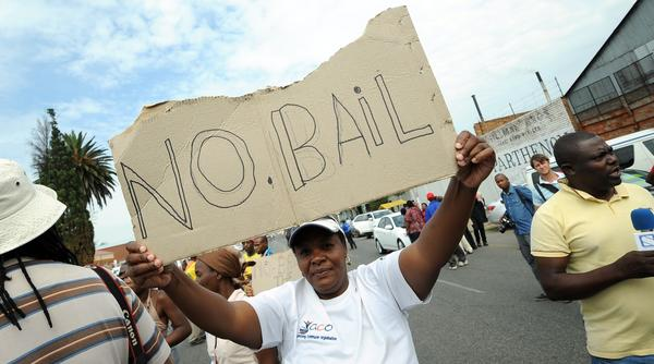 Protesters stand outside the Benoni court on Friday calling for no bail for the police officers charged with murdering Mido Macia.