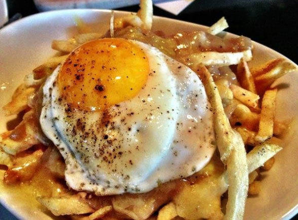Cheesy fries with gravy and a fried egg on top.