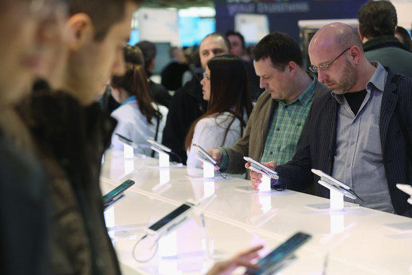 Visitors try out smartphones at the Samsung stand at the 2013 CeBIT technology trade fair on March 5 in Hanover, Germany.