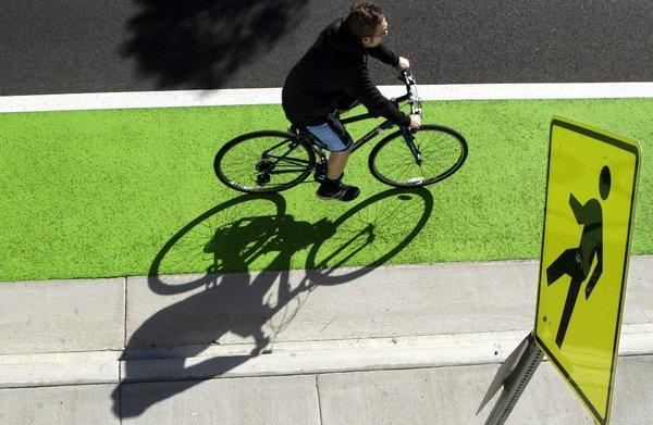 While Los Angeles tries to draw more cyclists to its streets with green lanes, other states are looking to tax them.