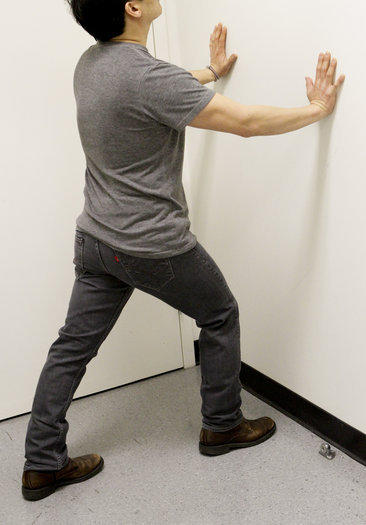 Help relieve heel pain with a calf stretch that involves keeping both heels on the ground while pushing against a wall.