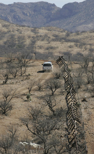 Feb. 28, 2007: A U.S. Border Patrol agent follows a vehicle barrier that defines the border to about four miles east of Sasabe, Ariz. Farther east there is no border barrier, but agents observe the remote desert area with aerial drones and ground sensors.