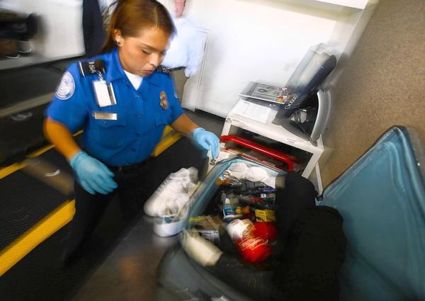 A TSA officer at Los Angeles International Airport hand inspects a traveler's baggage in March 2011 after an alarm sounded on one of the X-ray machines. Screeners at LAX fill boxes with about 1,400 pocket knives per month.