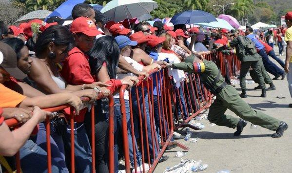 Venezuelan soldiers brace against protective fences as supporters wait in line to pay last respects to the late Venezuelan President Hugo Chavez outside the Military Academy in Caracas.