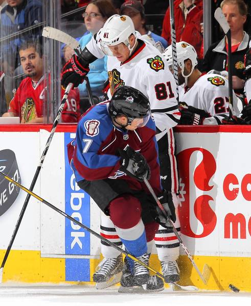 Avalanche's John Mitchell and Marian Hossa collide as they battle for control of the puck at the Pepsi Center.