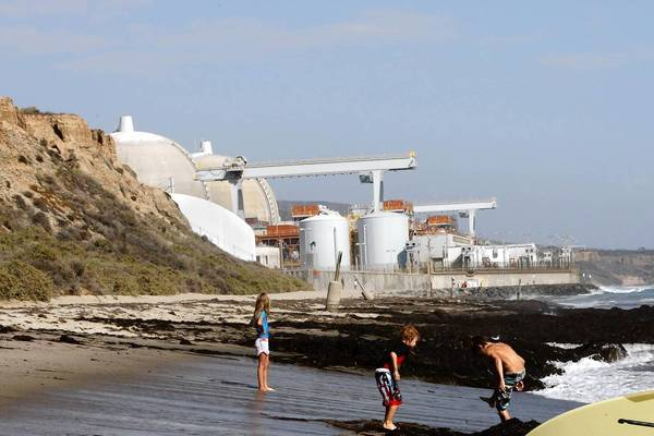 Surfers and swimmers at the seashore near the San Onofore nuclear power plant. A report on the root causes of problems at the plant shows that officials considered making design changes to its new steam generators before they were installed but rejected some fixes in part because they might require further regulatory approvals.