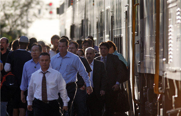 Commuters pour out of a Metrolink train at a busy station just east of Harbor Boulevard in Fullerton.