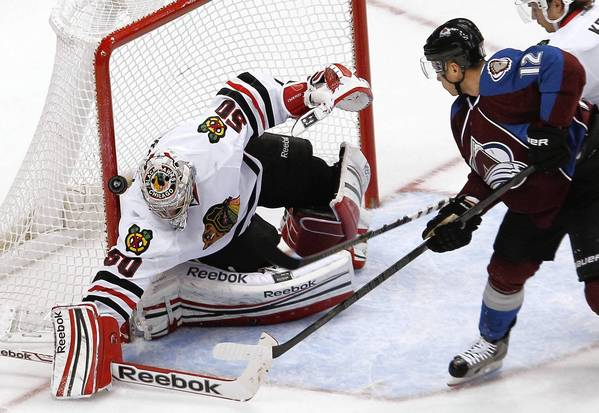 Goalie Corey Crawford has the puck bounce off the pipe on a shot on goal by the Avalanche's Chuck Kobasew.