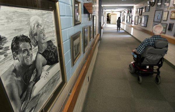 Hal Alexander, 87, a former TV stage manager and associate director, operates his motorized wheelchair past a photograph of actors Cary Grant and Doris Day, in a hallway at the Motion Picture & Television Fund nursing home and hospital in Woodland Hills.