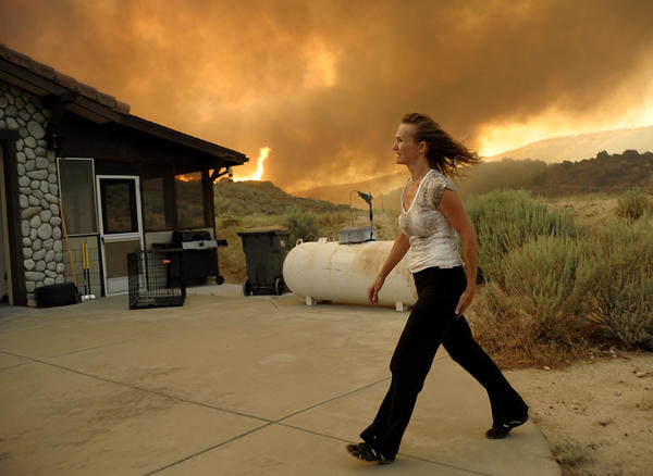 An unidentified woman watches as flames approach her home from a fast moving wildfire near Palmdale.