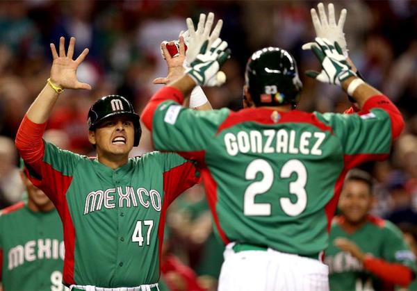 Luis Cruz and Adrian Gonzalez celebrate after Gonzalez's two-run home run against the U.S.