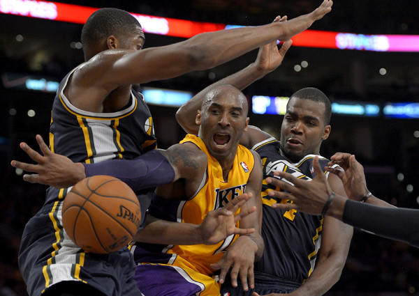 Kobe Bryant makes a pass after driving down the lane against Jazz big men Derrick Favors and Paul Millsap during a game earlier this season at Staples Center.