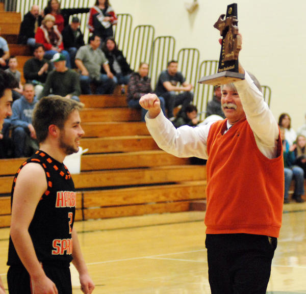 Harbor Springs boys' basketball coach Geoff Morse (right) hoists the Class C district championship trophy in front of junior Mitch Wallin Friday after the Rams defeated Manistique, 73-49, in the district championship game Friday at Manistique High School. The Rams, 11-11, will face Negaunee, 21-1, in a regional semifinal at 6 p.m. Monday, March 11, at the Escanaba High School gym.
