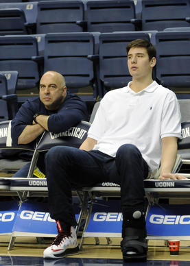 Huskies forward Tyler Olander (10) sits on the bench as his team warms up before their game against Providence at Gampel Pavilion. Olander broke his foot in a game against South Florida and didn't play.
