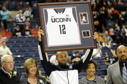Connecticut Huskies guard R.J. Evans (12) holds up his framed jersey next to his family during Senior Night ceremonies at Gampel Pavilion before their season finale against Providence Saturday afternoon.