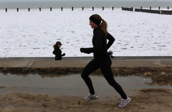 Pedestrians jog near puddles next to a icy Lake Michigan on Saturday. Rain and warmer temperatures are expected for Sunday.