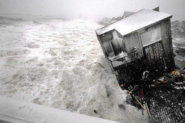 A house on the Plum Island seacoast in Newbury, Mass., sits precariously over the churning surf, driven by winds from a slow-moving winter storm.