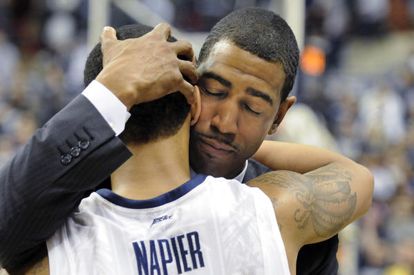 UConn coach Kevin Ollie hugs guard Shabazz Napier after the Huskies defeated Providence 63-59 in overtime at Gampel Pavilion in their season finale Saturday. It was the end of Ollie's first season as head coach.