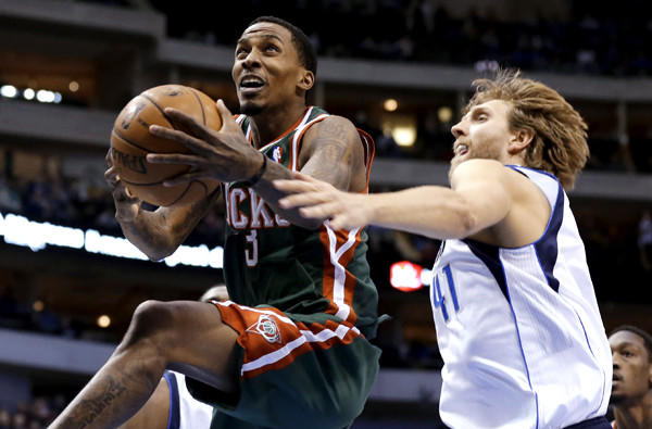 Milwaukee Bucks point guard Brandon Jennings gets past Mavericks power forward Dirk Nowitzki for a layup in a game at Dallas.