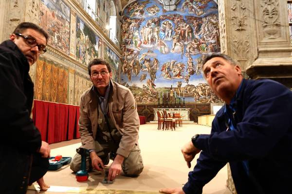 Workers set up the Sistine Chapel in preparation for the papal conclave, to begin Tuesday, to elect a successor to Benedict XVI, who resigned Feb. 28.