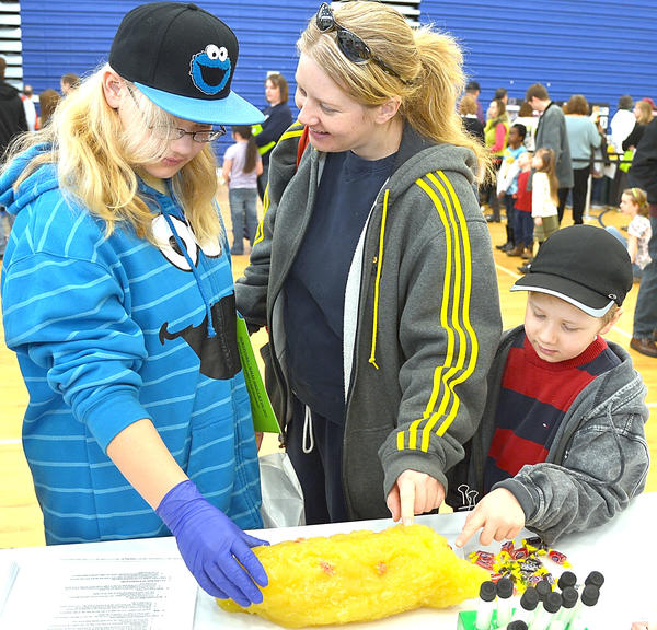 Aurora Florek and her mom Marguerite Florek talk about a 5 lb. hunk of simulated fat Saturday at the 30th annual Waynesboro Hospital Health Fair at Waynesboro High School. Brother Andrew Florek tests the squishy blob.