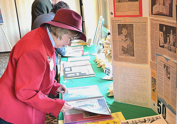 Florence Grant thumbs through a scrapbook of press clippings of past book sales for the local American Association of University Women. The club celebrated 50 years of book sales with a luncheon at Fountain Head Country Club.