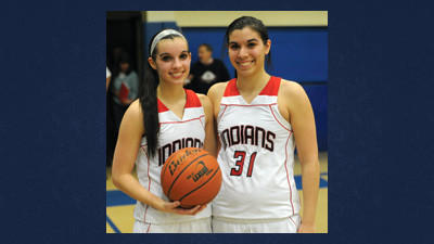 Lady Indians' Lyndy Baer shares a moment with twin sister Carly Baer (31) after achieving the 1,000-point milestone in their Class A first round victory over Quigley Catholic Saturday.