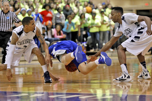 Christopher Newport University's Paul Meredith, center, falls to the court between the defense of Virginia Wesleyan College's Tre' Ford, left, and Trent Batson during Saturday's second round Division III NCAA tournament game.