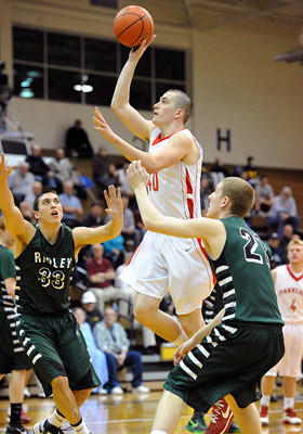 Parkland's Nicholas Selvaggi (center) drives to the basket in between Ridley's Steve Plousis (left) and Jon McGill (right) in the first round of the PIAA 4A boys basketball tournament Saturday at Allen High School.