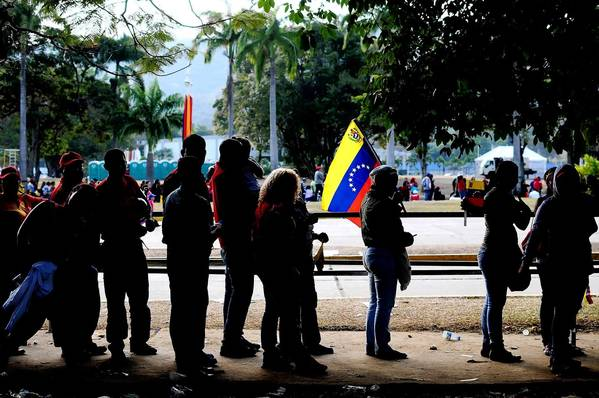 People wait to view the body of President Hugo Chavez at the military academy in Caracas, Venezuela's capital. An election for his successor is set for April 14.