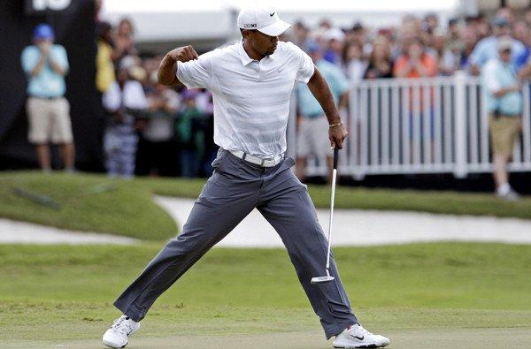 Tiger Woods pumps his fist after making a birdie putt on the 18th hole Saturday during the third round of the Cadillac Championship.