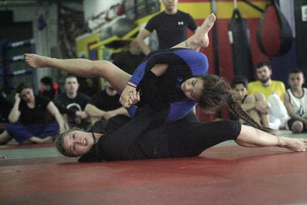 UFC women's bantamweight champion Ronda Rousey demonstrates a move with Caitlin Cardenas during an MMA workshop, which took place at the Glendale Fighting Club on Saturday.