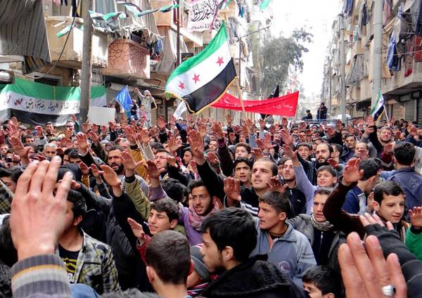 An amateur photo shows protesters holding Syrian revolution flags during a demonstration against the Syrian regime in Aleppo.