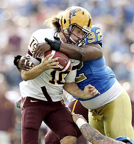 Bruins defensive tackle Brian Price wraps up Arizona State quarterback Samson Szakacsy for a sack in the first half Saturday.