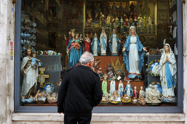 A man looks in a window at religious memorabilia in a shop window across from St. Peter's Square on Sunday in Vatican City, Vatican. Cardinals are set to enter the conclave to elect a successor to Pope Benedict XVI after he became the first pope in 600 years to resign from the role. The conclave is scheduled to start on March 12 inside the Sistine Chapel and will be attended by 115 cardinals as they vote to select the 266th Pope of the Catholic Church.
