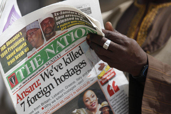 A man in Kano, Nigeria, reads a local newspaper report on the fate of kidnapped construction workers.